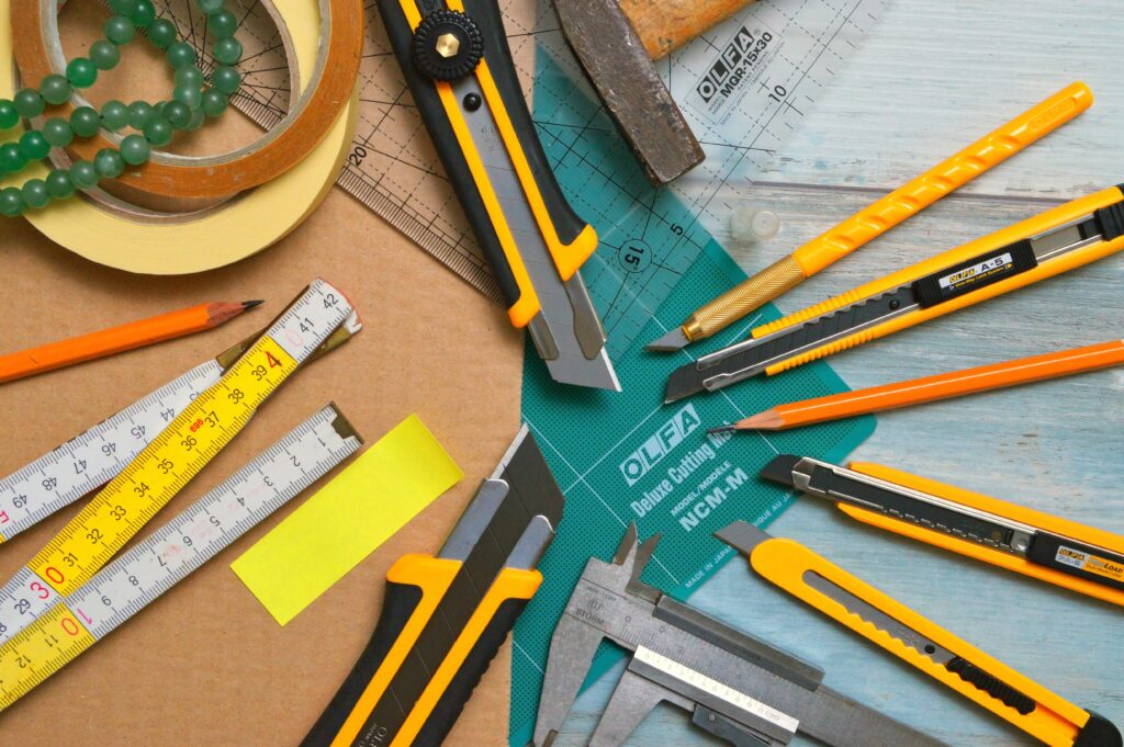 Measuring tape, exacto knives, tape, and pencils