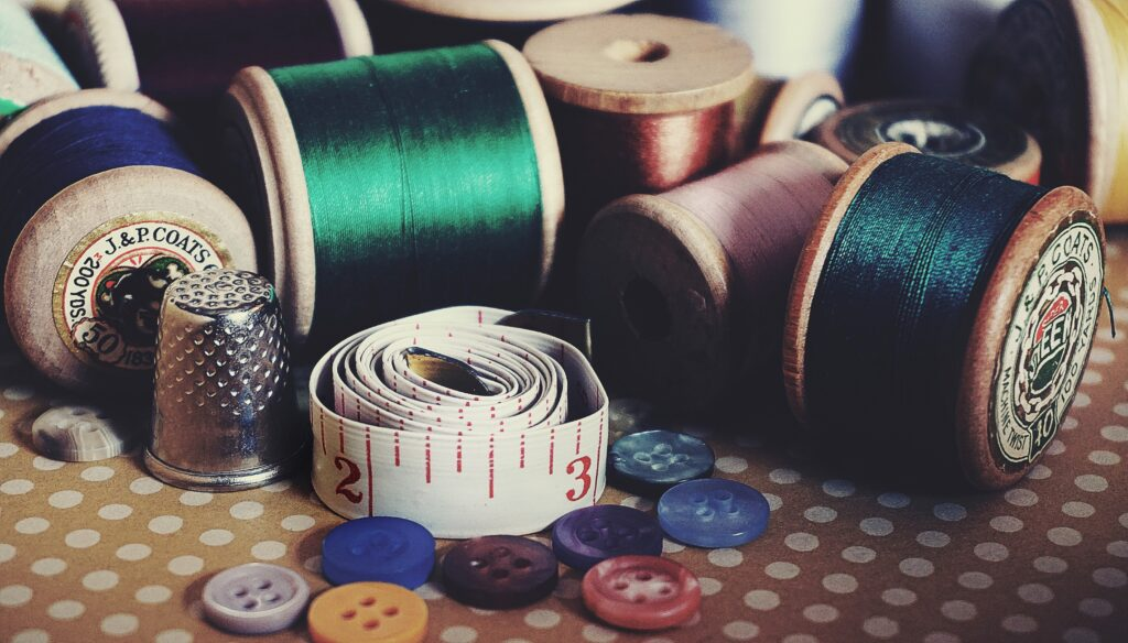 Spools of thread, buttons, a thimble, and a tailor's tape measure.