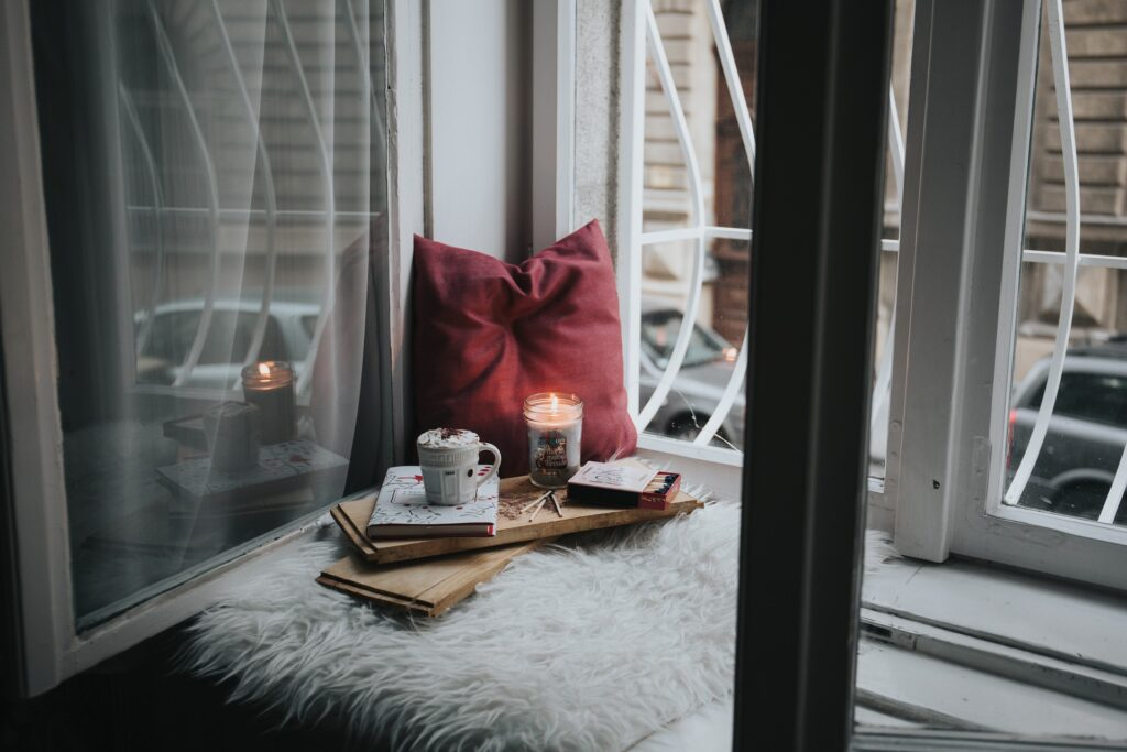 Pillow and candle by an open window
