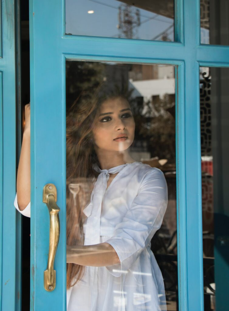 Young woman staring out through door's glass pane.